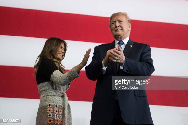 President Donald Trump applauds he arrives with his wife Melania Trump to speak to US military personnel at Yokota Air Base at Fussa in Tokyo on...