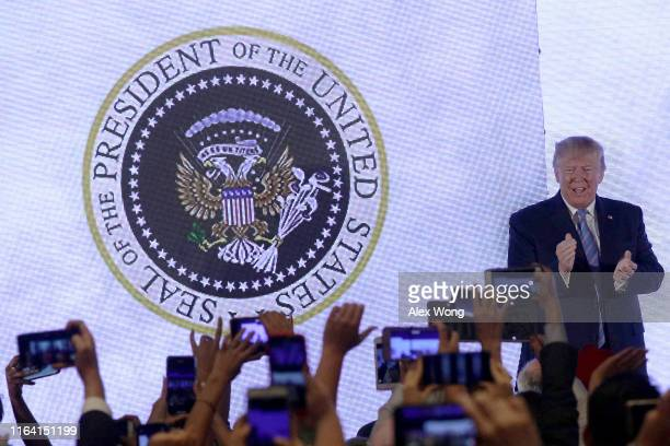 President Donald Trump applauds in front of a doctored presidential seal with a double headed eagle and a set of golf clubs as he arrives to address...