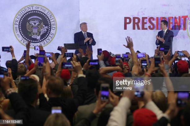 S President Donald Trump applauds in front of a doctored presidential seal with a double headed eagle and a set of golf clubs as founder and...