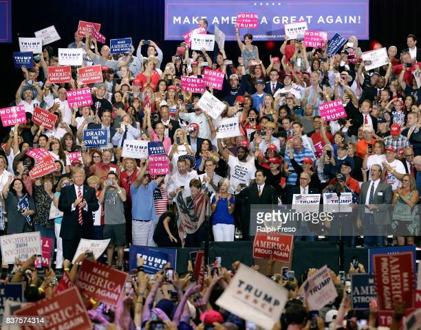 S President Donald Trump applauds the crowd of supporters at the Phoenix Convention Center as he takes the stage during a rally on August 22 2017 in...