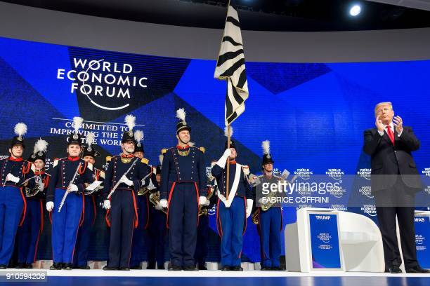 US President Donald Trump applauds the Landwehr Fribourg band before delivering his speech during the World Economic Forum annual meeting on January...