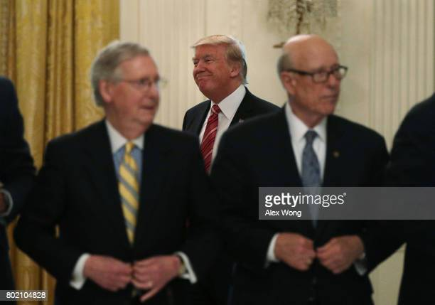 S President Donald Trump arrives at the East Room of the White House as Senate Majority Leader Sen Mitch McConnell and Sen Pat Roberts wait for the...