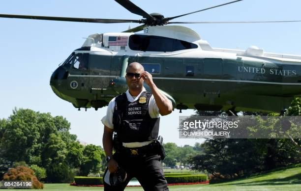 US President Donald Trump arrives on Marine One as a member of the Secret Service stands guard at the White House on May 17 2017 in Washington DC /...