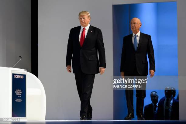 US President Donald Trump arrives on stage followed by Founder and Executive Chairman of the World Economic Forum Klaus Schwab before delivering his...