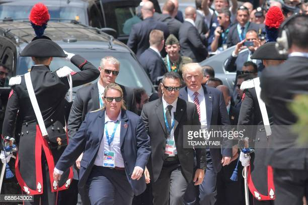 US President Donald Trump arrives surrounded by bodyguards at the ancient Greek Theatre of Taormina during the Heads of State and of Government G7...