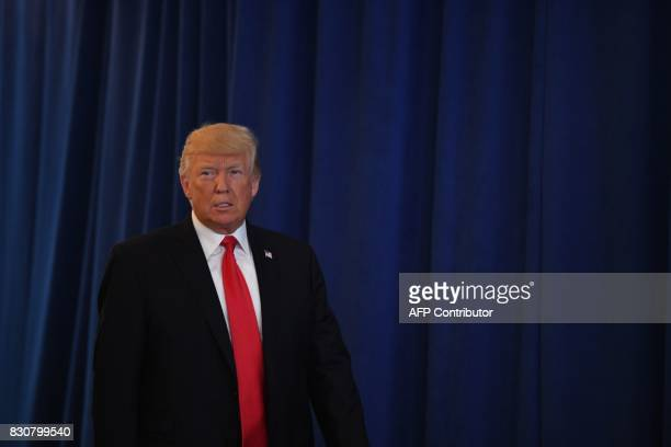 US President Donald Trump arrives to speak to the press about protests in Charlottesville on August 12 at Trump National Golf Club in Bedminster New...