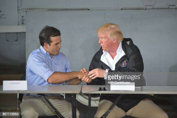 US President Donald Trump attends a meeting with Governor Ricardo Rossello and other officials after stepping off Air Force One upon arrival at Luis...