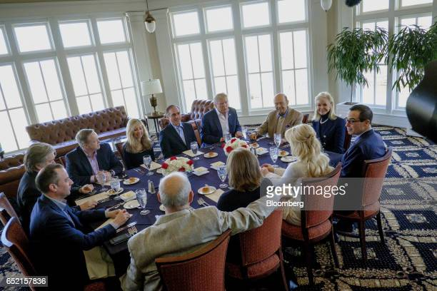 US President Donald Trump back center speaks with members of his cabinet and their significant others during a working lunch at the Trump National...