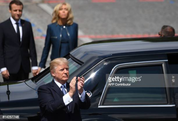 US President Donald Trump bids farewell flanked by French President Emmanuel Macron and his wife Brigitte Macron as he leaves the annual Bastille Day...