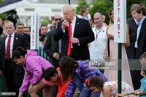 S President Donald Trump blows a whistle to kickoff a race during the 139th Easter Egg Roll with Trump's daughter Tiffany Trump on the South Lawn of...