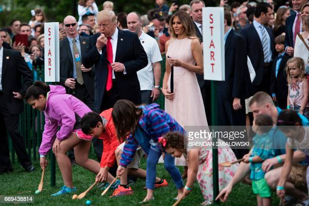US President Donald Trump blows a whistle to start a race during the Easter Egg Roll on the South Lawn of the White House April 17 2017 in Washington...