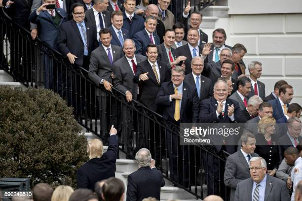 US President Donald Trump bottom left gestures toward members of congress after speaking during a tax bill passage event with Republican...