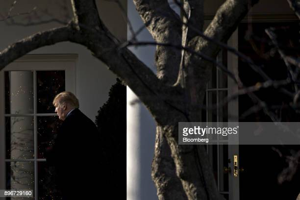 US President Donald Trump bottom left walks near the Oval Office of the White House before boarding Marine One in Washington DC US on Thursday Dec 21...