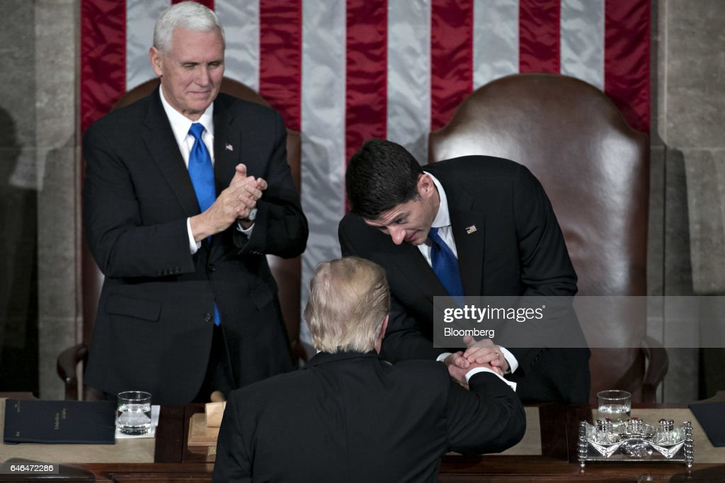 U.S. President Donald Trump, bottom, shakes hands with U.S. House Speaker Paul Ryan, a Republican from Wisconsin, as U.S. Vice President Mike Pence, left, applauds during a joint session of Congress in Washington, D.C., U.S., on Tuesday, Feb. 28, 2017. Trump will press Congress to carry out his priorities for replacing Obamacare, jump-starting the economy and bolstering the nations defenses in an address eagerly awaited by lawmakers, investors and the public who want greater clarity on his policy agenda. Photographer: Andrew Harrer/Bloomberg via Getty Images