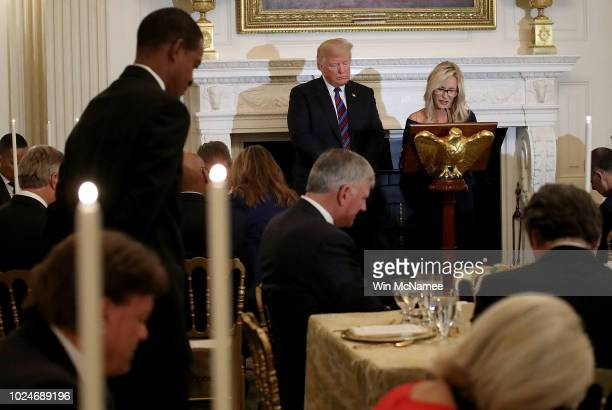 S President Donald Trump bows his head as Pastor Paula White delivers a prayer before dinner for guests celebrating evangelical leadership at the...