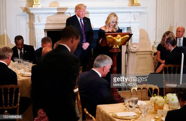 US President Donald Trump bows his head as Pastor Paula White reads a prayer at an event honoring Evangelical leadership in the State Dining Room of...
