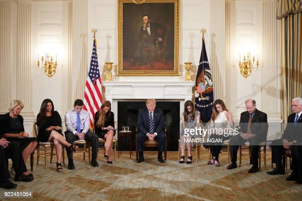 US President Donald Trump bows his head during a prayer before taking in a listening session on gun violence with teachers and students in the State...