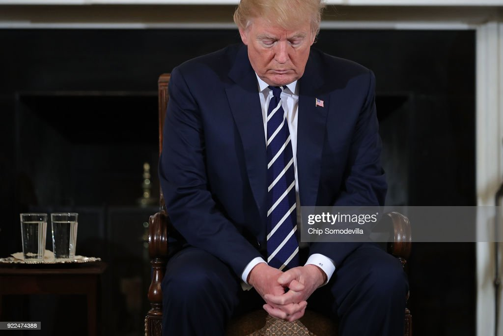 U.S. President Donald Trump bows his head in prayer during a listening session with students, parents and teachers in the State Dining Room at the White House February 21, 2018 in Washington, DC. Trump is hosting the session in the wake of last week's mass shooting at Marjory Stoneman Douglas High School in Parkland, Florida, that left 17 students and teachers dead.