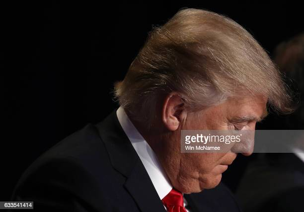 US President Donald Trump bows his head in prayer while attending the National Prayer Breakfast February 2 2017 in Washington DC Every US president...