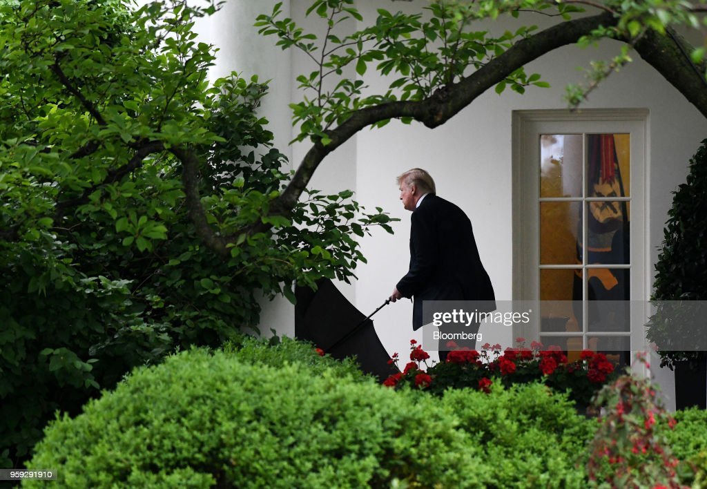 U.S. President Donald Trump carries an umbrella while leaving the White House in Washington, D.C., U.S., on Wednesday, May 16, 2018. Trumpcontinued to defend the lifeline he offered to Chinese telecom-equipment maker ZTE Corp., insisting trade talks with Beijing are just getting started. Photographer: Olivier Douliery/Pool via Bloomberg