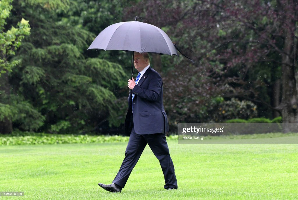 U.S. President Donald Trump carries an umbrella while walking on the South Lawn of the White House before boarding Marine One in Washington, D.C., U.S., on Wednesday, May 16, 2018. Trump is visiting Walter Reed where Melania Trump underwent successful surgery to treat a kidney condition on Monday. Photographer: Olivier Douliery/Pool via Bloomberg