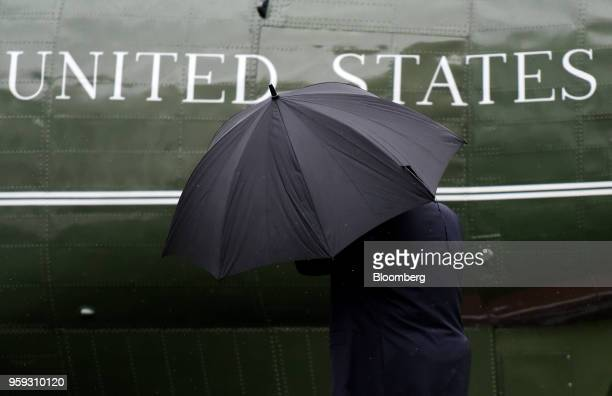 US President Donald Trump carries an umbrella while walking on the South Lawn of the White House before boarding Marine One in Washington DC US on...