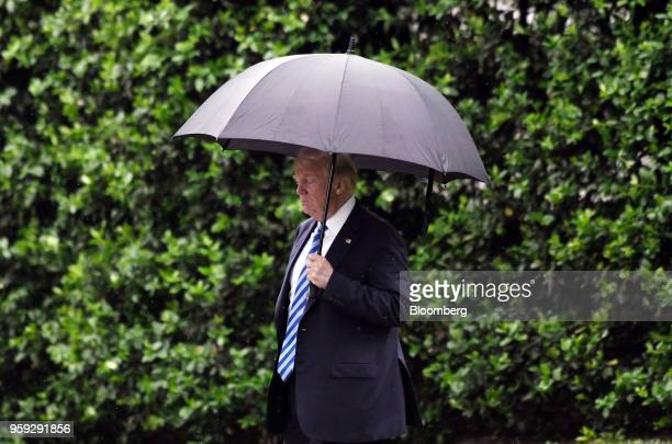 US President Donald Trump carries an umbrella while walking towards Marine One to depart from the White House in Washington DC US on Wednesday May 16...