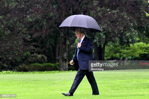 S President Donald Trump carries an umbrella while walking towards Marine One to depart from the White House in Washington DC US on Wednesday May 16...