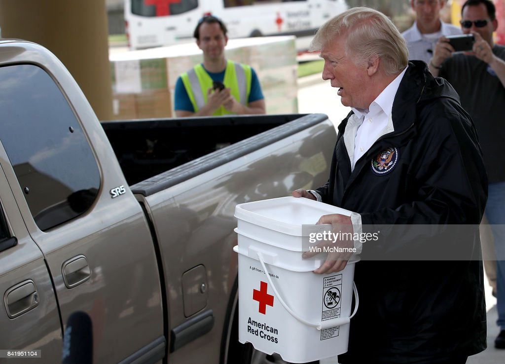 U.S. President Donald Trump carries emergency supplies to a waiting pickip truck for residents impacted by Hurricane Harvey while visiting the First Church of Pearland September 2, 2017 in Pearland, Texas. Pearland, just south of Houston, was heavily damaged by the floodwaters created by the hurricane.