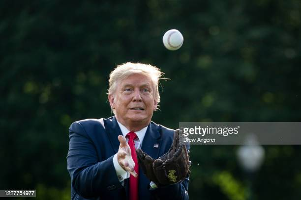 President Donald Trump catches a baseball thrown by former New York Yankees Hall of Fame pitcher Mariano Rivera on the South Lawn of the White House...