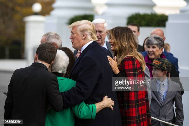 US President Donald Trump center and First Lady Melania Trump center right take photos with guests after viewing the White House Christmas tree at...