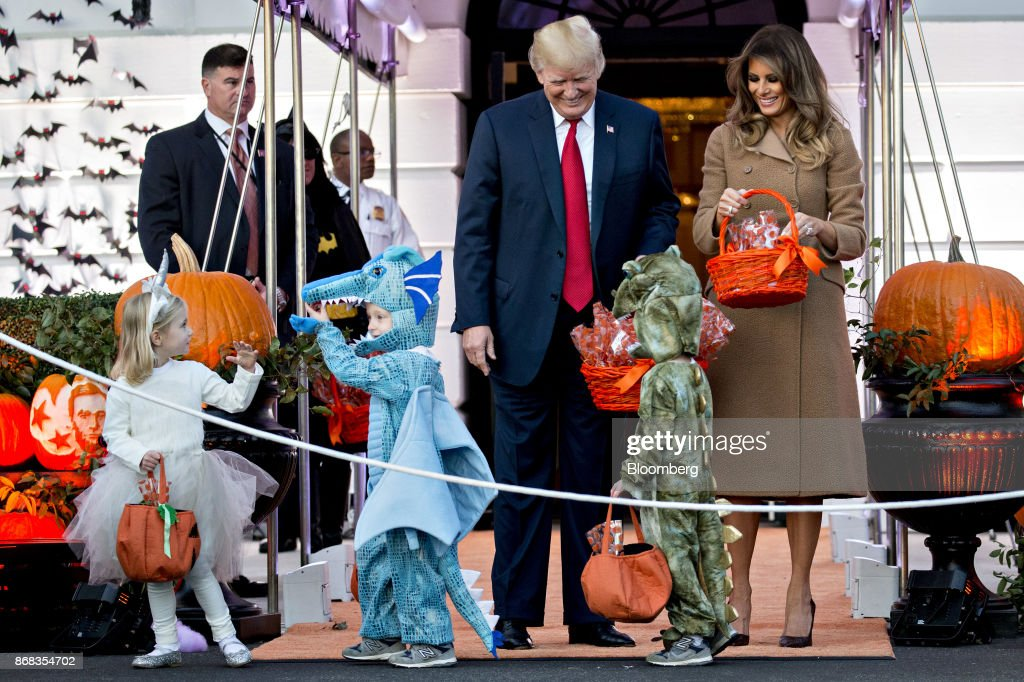 U.S. President Donald Trump, center, and U.S. First Lady Melania Trump, right, greet children dressed up in costumes during a Halloween event on the South Lawn of the White House in Washington, D.C., U.S., on Monday, Oct. 30, 2017. Trump greeted costumed children during a traditional Halloween trick-or-treat at the White House, on the same day as Special Counsel Robert Mueller's investigation took a major turn as authorities charged three people -- a former campaign chief, his business associate and an ex-policy adviser -- with crimes including money laundering, lying to the FBI and conspiracy. Photographer: Andrew Harrer/Bloomberg via Getty Images