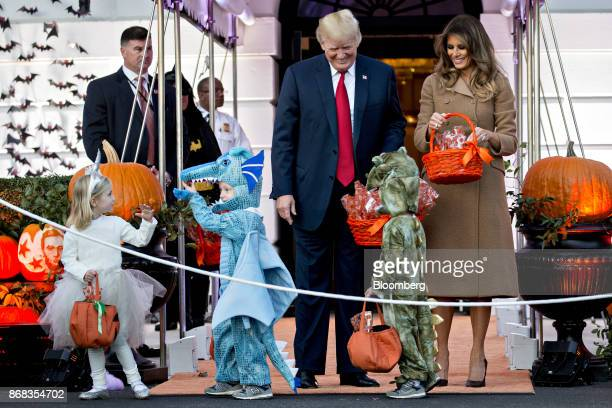 US President Donald Trump center and US First Lady Melania Trump right greet children dressed up in costumes during a Halloween event on the South...