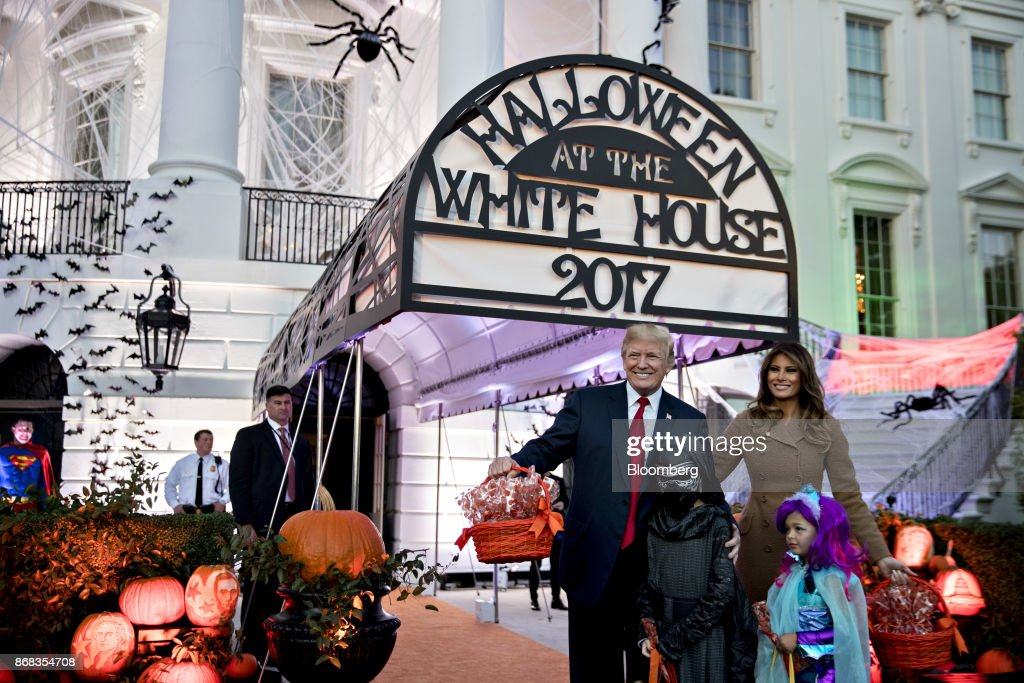 U.S. President Donald Trump, center, and U.S. First Lady Melania Trump, right, pose for a photograph with children dressed up in costumes during a Halloween event on the South Lawn of the White House in Washington, D.C., U.S., on Monday, Oct. 30, 2017. Trump greeted costumed children during a traditional Halloween trick-or-treat at the White House, on the same day as Special Counsel Robert Mueller's investigation took a major turn as authorities charged three people -- a former campaign chief, his business associate and an ex-policy adviser -- with crimes including money laundering, lying to the FBI and conspiracy. Photographer: Andrew Harrer/Bloomberg via Getty Images