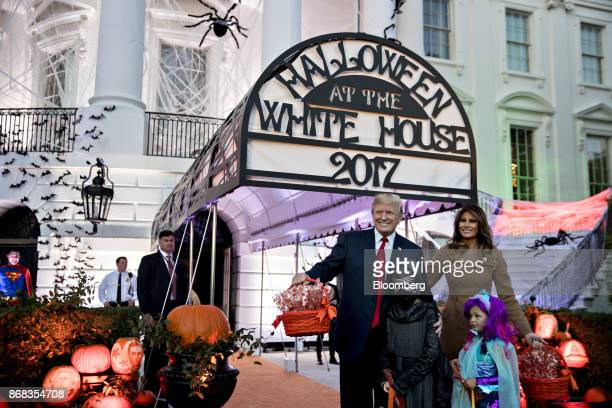 US President Donald Trump center and US First Lady Melania Trump right pose for a photograph with children dressed up in costumes during a Halloween...