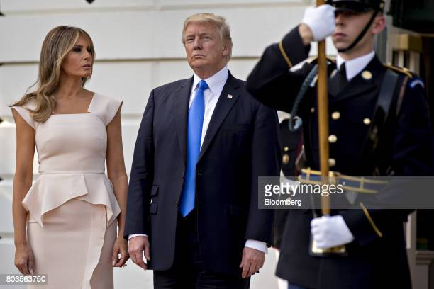 US President Donald Trump center and US First Lady Melania Trump stand at the South Portico of the White House to greet Moon Jaein South Korea's...
