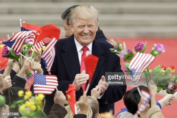 US President Donald Trump center and Xi Jinping China's president greet attendees waving American and Chinese national flags during a welcome...