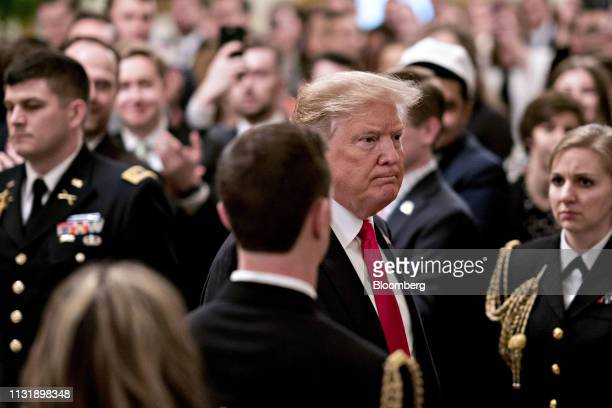 US President Donald Trump center arrives to an executive order signing event in the East Room of the White House in Washington DC US on Thursday...