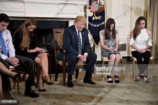 US President Donald Trump center bows his head during a prayer at a listening session on gun violence with high school students teachers and parents...