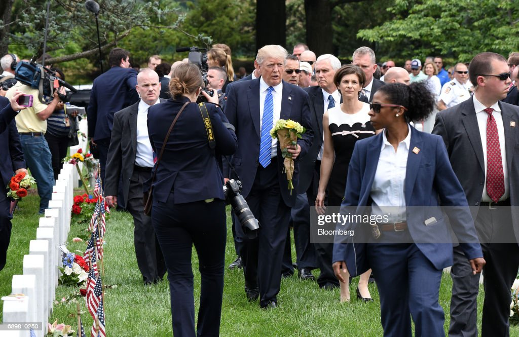 U.S. President Donald Trump, center, carries flowers in Section 60 of Arlington National Cemetery in Arlington, Virginia, U.S., on Monday, May 29, 2017. On Memorial Day, Trump visited Arlington National Cemetery to honor the memory of fallen service men and women. Photographer: Olivier Douliery/Pool via Bloomberg