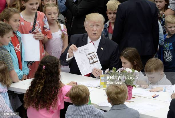 US President Donald Trump center displays a card made for members of the military during the annual Easter Egg Roll on the South Lawn of the White...