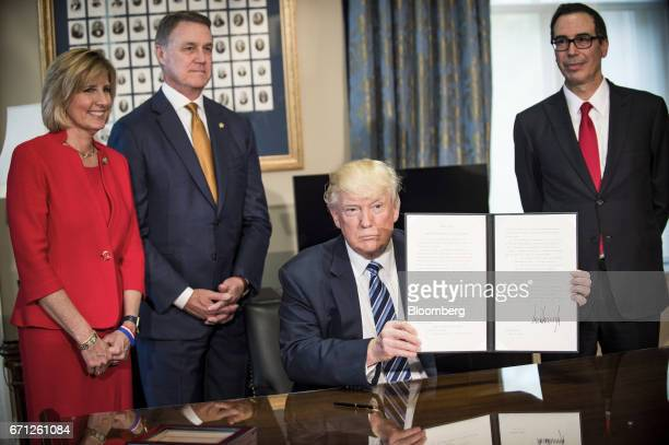 US President Donald Trump center displays a signed directive on tax and Wall Street regulations as Steven Mnuchin US Treasury secretary right...