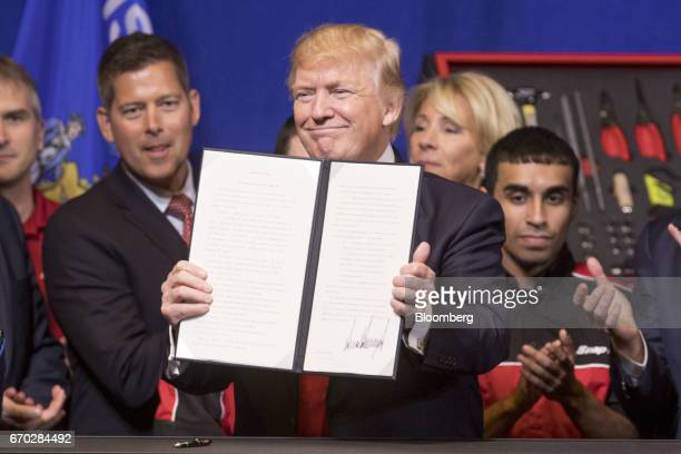 US President Donald Trump center displays a signed executive order during an event at SnapOn Tools Corp headquarters in Kenosha Wisconsin US on...