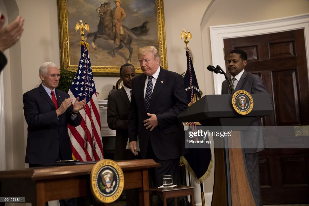 U.S. President Donald Trump, center, finishes speaking while U.S. Vice President Mike Pence, from left, Ben Carson, U.S. Secretary of Housing and Urban Development, and Martin Luther King Jr.'s nephew Isaac Newton Farris Jr., chief executive officer of the Martin Luther King Jr. Center for Non-Violent Social Change, react before the signing of a proclamation in the Roosevelt Room of the White House in Washington, D.C., U.S., on Friday, Jan. 12, 2018. Trump blew up negotiations on a potential immigration deal, pushing both sides to harden their positions and raising the risks that the standoff will sink talks aimed at averting a government shutdown at the end of next week. Photographer: Eric Thayer/Bloomberg via Getty Images