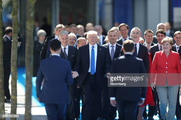 US President Donald Trump center gestures while walking with other world leaders as Emmanuel Macron France's president right arrives at a summit at...