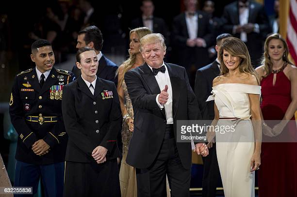 US President Donald Trump center gives the audience of service members a thumbs up as First Lady Melania Trump attends the Armed Services Inaugural...