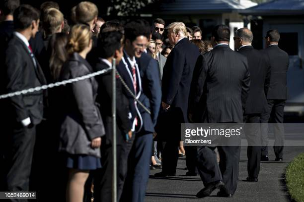 US President Donald Trump center greets visitors before boarding Marine One on the South Lawn of the White House in Washington DC US on Thursday Oct...