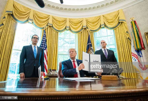 US President Donald Trump center holds up a signed executive order imposing sanctions on Iran's supreme leaderAyatollah Ali Khamenei in the Oval...