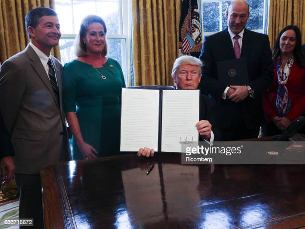 US President Donald Trump center holds up a signed Executive Order related to the review of the DoddFrank Act in the Oval Office of the White House...