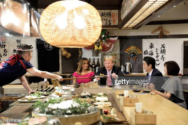 President Donald Trump, center, is served a baked potato with butter while sitting at a counter with First Lady Melania Trump, second left, Shinzo...